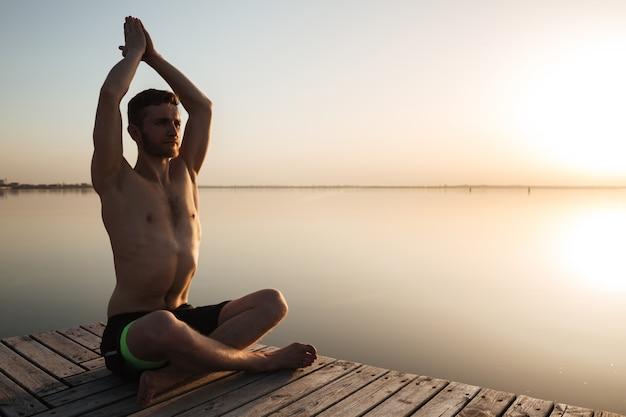 Konzentrierte junge sportler machen yoga-meditationsübungen