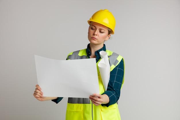 Konzentrierte junge weibliche bauarbeiterin, die schutzhelm und sicherheitsweste hält, die papiere hält, die eins betrachten