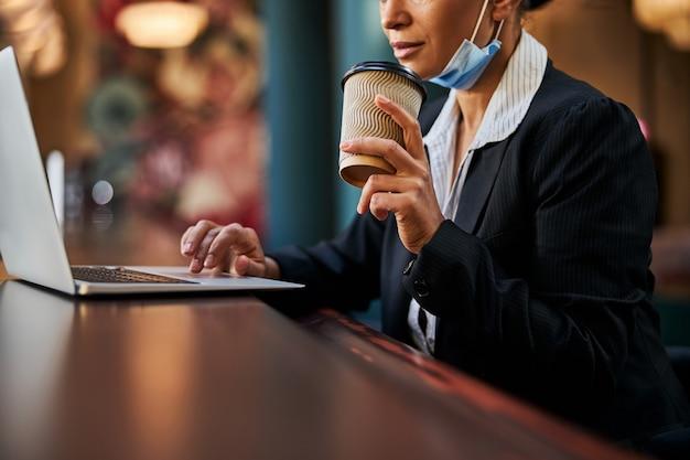 Konzentrierte junge weibliche person, die vor ihrem laptop sitzt und nachrichten im chat liest