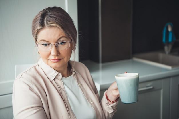 Konzentrierte kaukasische frau mit brille, die eine tasse tee trinkt und fern von zu hause aus arbeitet