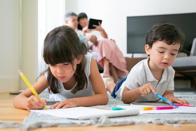 Konzentrierte kleine jungen und mädchen, die auf dem boden liegen und im wohnzimmer zeichnen, während eltern zusammensitzen