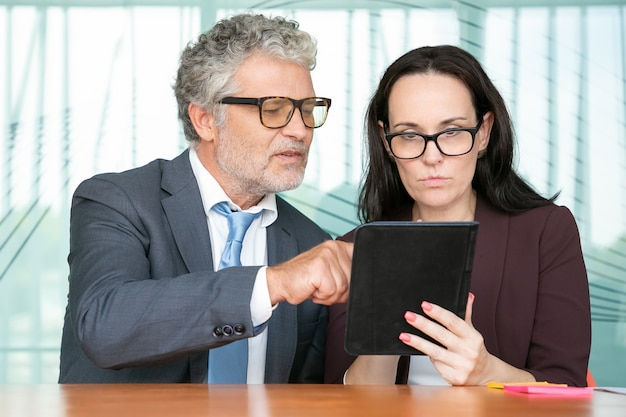 Konzentrierte kollegen, die gemeinsam die präsentation auf dem tablet betrachten und auf den bildschirm schauen, während sie im büro am tisch sitzen.