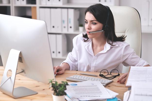 Konzentrierte kundendienstmitarbeiterin, die am schreibtisch sitzt und computer benutzt, während sie mit kunden arbeitet