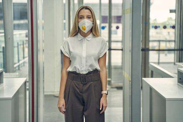 Konzentrierte langhaarige frau, die bei der flugvorbereitung am metalldetektor steht und am flughafen eine medizinische maske trägt