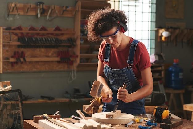 Konzentrierte lockige frau in gehörschutz und schutzbrille mit hammer und meißel bei der arbeit mit holzbrett