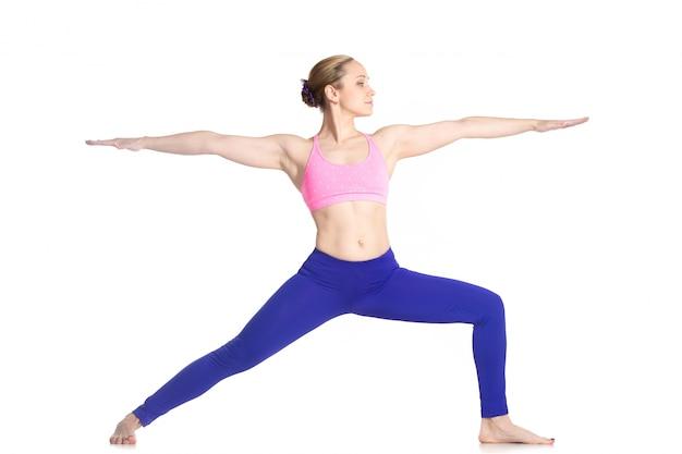 Konzentrierte mädchen praktizieren yoga krieger stellen