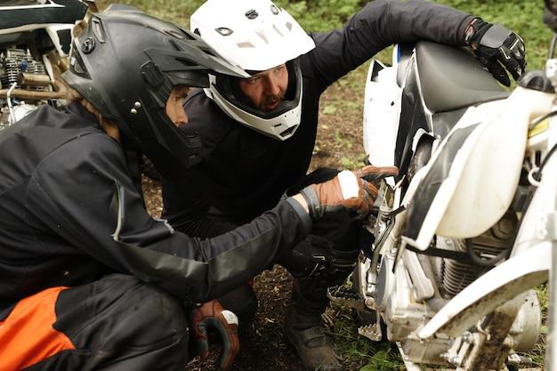 Konzentrierte motorradfahrer in helmen untersuchen die bauchwanne des motorrads, während sie den grund der panne besprechen