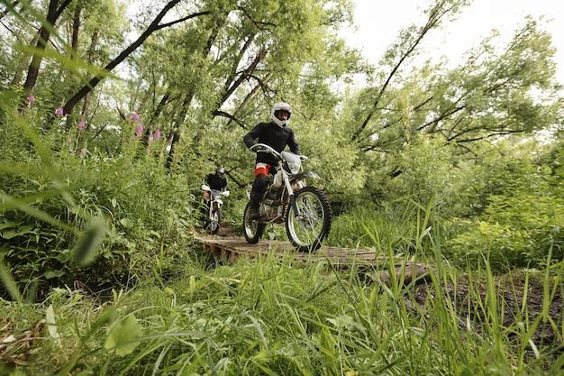 Konzentrierte motorradfahrer in schutzkleidung überqueren die zerbrechliche holzbrücke, während sie am motorradwettbewerb teilnehmen