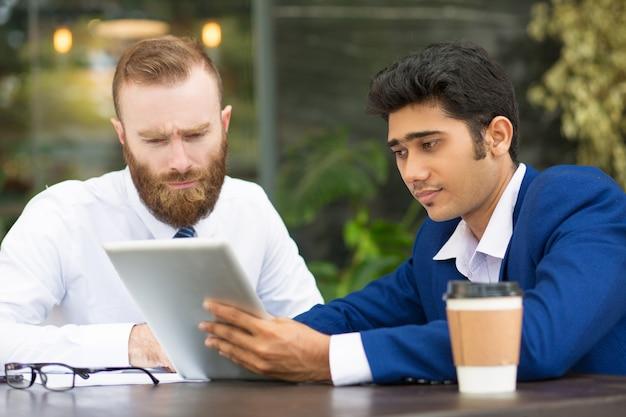 Konzentrierte multiethnische geschäftspartner mit tablet