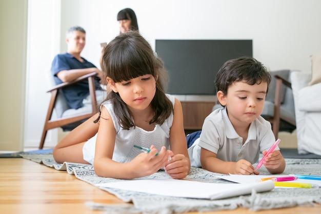 Konzentrierte niedlichen kleinen bruder und schwester, die auf dem boden liegen und im wohnzimmer zeichnen, während eltern zusammen sitzen