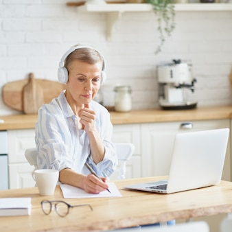 Konzentrierte reife frau mit kopfhörern, die in der küche sitzt und sich notizen macht, um online auf dem laptop zu lernen?