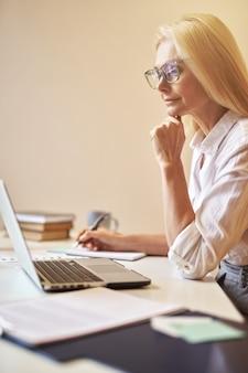 Konzentrierte reife geschäftsfrau mit brille, die beschäftigt aussieht, während sie mit dem laptop notizen macht, die in der arbeit arbeiten?