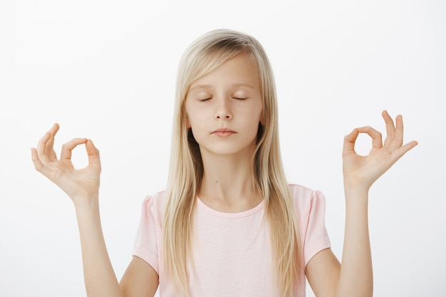 Konzentrierte ruhige europäische mädchen versuchen meditation mit mutter. porträt des selbstbewussten gutaussehenden kindes mit blondem haar, schließenden augen und stehend über grauer wand in yoga-pose mit zen-gesten