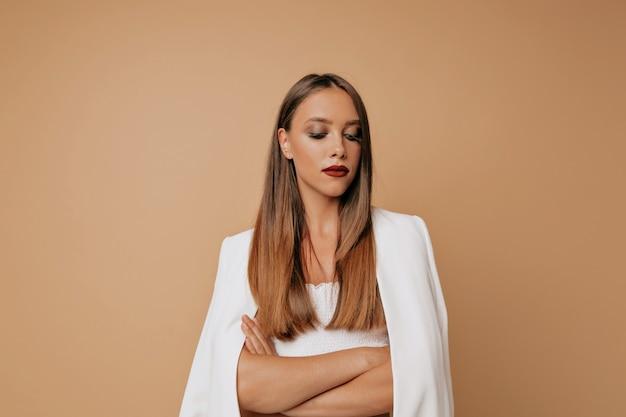 Konzentrierte schöne dame gekleidete weiße kleidung mit abend make-up blick nach unten