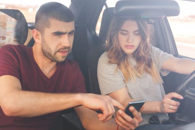 Konzentrierte schöne frau und ehemann schauen aufmerksam auf smartphone, nutzen online-karten, fahren in fremde länder. frau am steuer, mann neben ihr auf dem vordersitz. menschen, fahren, ziel