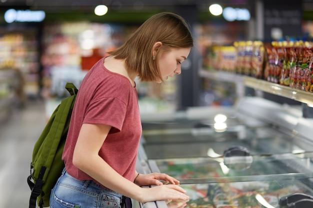 Konzentrierte schöne weibliche teenager, die eis kaufen kauft, lehnt sich am kühlschrank im supermarkt, trägt rucksack, gekleidet in freizeitkleidung, hat ernstes aussehen. menschen, konsum und kaufkonzept