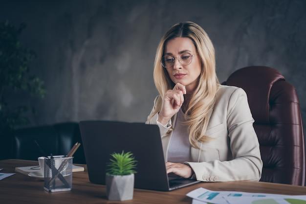 Konzentrierte selbstbewusste kluge kluge dame, die das geschäftsproblem löst, das mit netbook am tisch sitzt