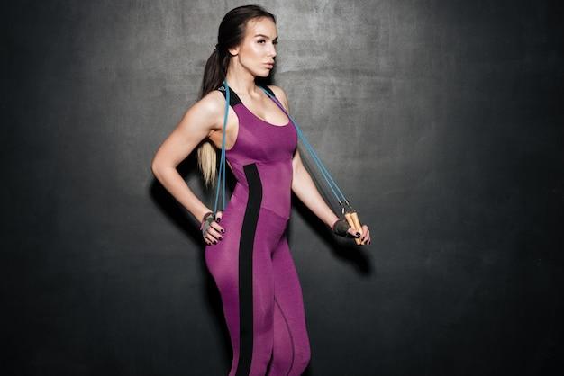 Konzentrierte sport junge dame, die springseil hält.