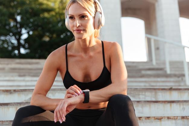 Konzentrierte starke junge sportfrau, die musik hört