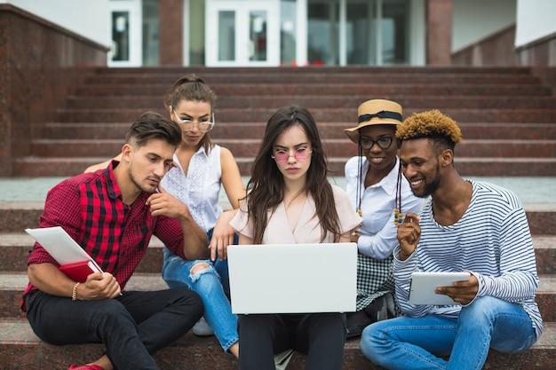 Konzentrierte studenten mit laptop draußen