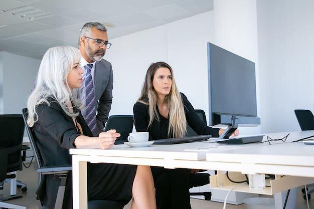 Konzentrierte unternehmensgruppe, die auf den pc-monitor starrt und die projektpräsentation am arbeitsplatz beobachtet. geschäftskommunikationskonzept