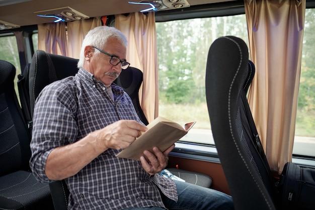 Konzentrierter älterer kaukasischer mann mit weißem haar liest ein buch, während er mit dem bus durch den wald fährt