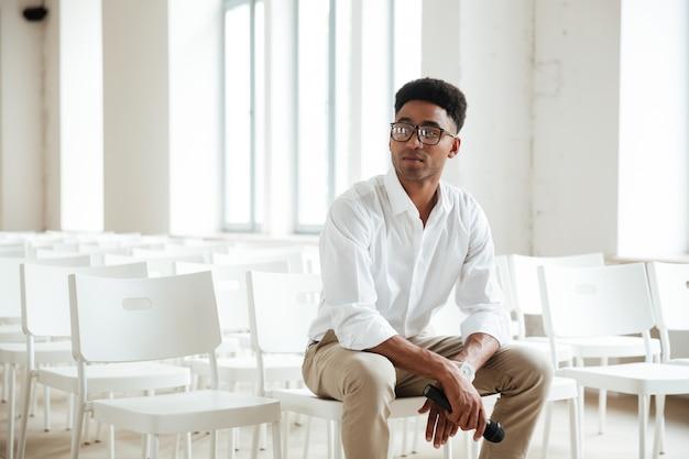 Konzentrierter afrikanischer mann, der im büro drinnen sitzt