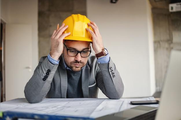 Konzentrierter architekt, der seinen kopf hält, sieht und blaupausen betrachtet