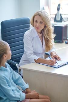 Konzentrierter arzt, der während der pädiatrischen sprechstunde am schreibtisch sitzt