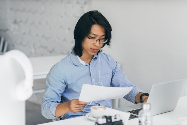 Konzentrierter asiatischer büroangestellter in kopfhörern, die dokumente am arbeitsplatz lesen. innenporträt des freiberuflichen chinesischen it-spezialisten trinkt kaffee, während er mit laptop verwendet.