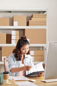 Konzentrierter asiatischer manager, der am schreibtisch mit computer sitzt und geschäftspapiere im büro analysiert