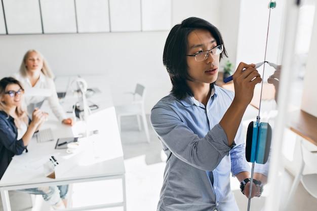 Konzentrierter asiatischer manager, der grafik während der präsentation auf flipchart zeichnet. innenporträt des chinesischen büroangestellten, der etwas auf weiße tafel schreibt, während seine kolleginnen zuschauen.