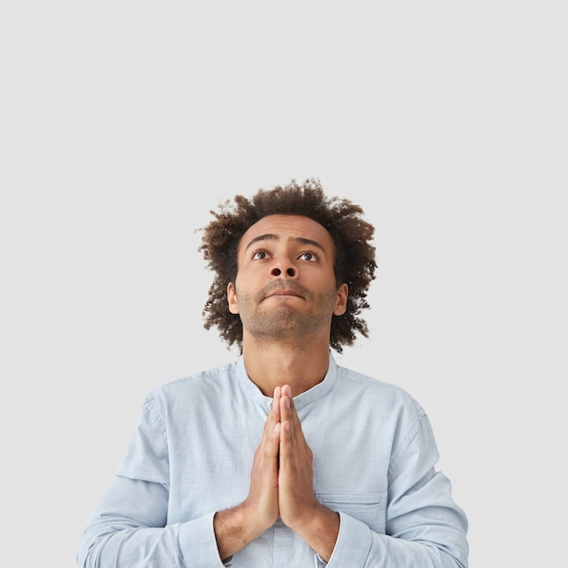 Konzentrierter attraktiver mann student macht gebetsgeste, schaut mit hoffnung nach oben