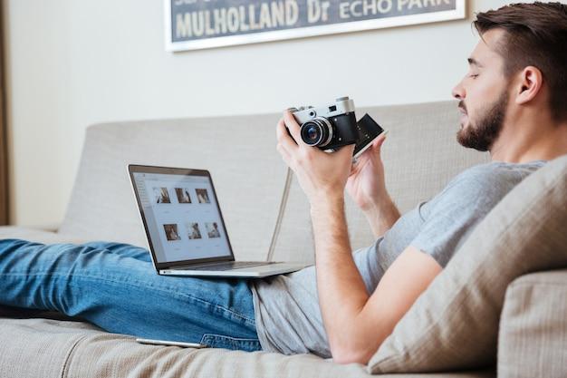 Konzentrierter attraktiver mannfotograf mit alter vintage-front und laptop auf dem sofa zu hause