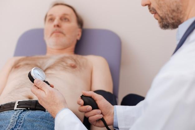 Konzentrierter, ausgezeichneter, erfahrener arzt, der einige tests mit einem tonometer zur überprüfung des allgemeinen gesundheitszustands seines patienten durchführt