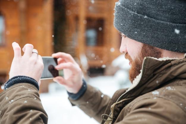 Konzentrierter bärtiger mann, der bei schneewetter im winter fotos mit dem handy macht