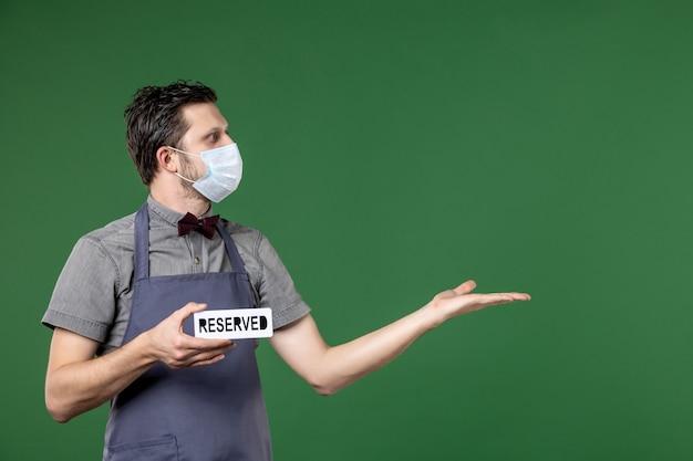 Konzentrierter bankettserver in uniform mit medizinischer maske und reserviertem symbol, das auf etwas auf der linken seite auf grünem hintergrund zeigt
