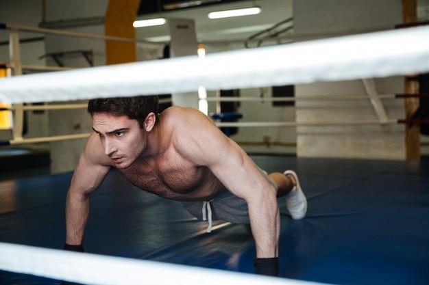 Konzentrierter boxer, der liegestütze im fitnessstudio macht