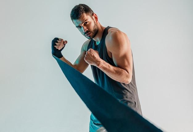 Konzentrierter boxer mit boxverband an der hand. junge bärtige europäische sportler tragen sportuniform und schauen in die kamera. auf grauem hintergrund mit türkisfarbenem licht isoliert. studioshooting