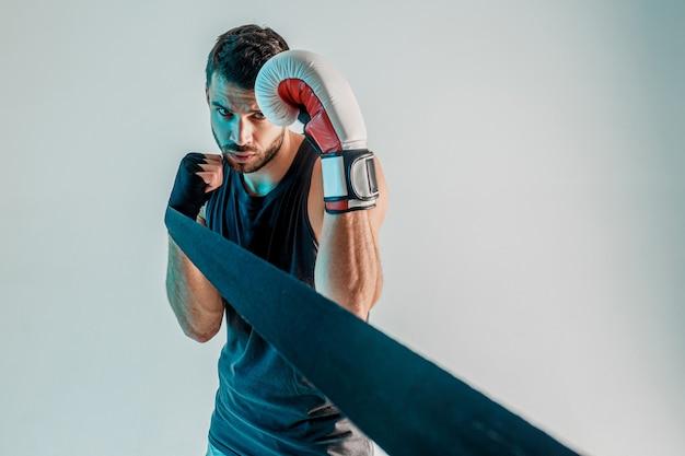 Konzentrierter boxer mit boxverband und handschuh an den händen. junge bärtige europäische sportler tragen sportuniform. auf grauem hintergrund mit türkisfarbenem licht isoliert. studio-shooting. platz kopieren