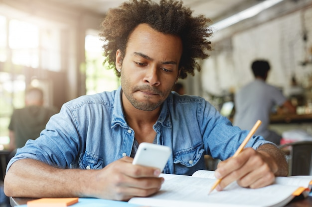 Konzentrierter dunkelhäutiger student mit afro-haaren, der hausaufgaben macht, am kantinentisch mit lehrbuch und heft sitzt und eine kleine pause macht, um textnachrichten auf seinem elektronischen gerät zu lesen