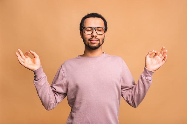Konzentrierter entspannter mann, der mit geschlossenen augen steht, sich beim meditieren entspannt und versucht, gleichgewicht und harmonie zu finden