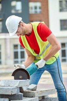 Konzentrierter, erfahrener baumeister mit schutzhelm und schutzbrille, der mit einer elektrischen kreissäge ein stück zementfliese abschneidet