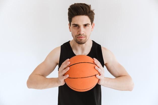 Konzentrierter ernster starker junger sportmannbasketballspieler, der ball lokalisiert hält.