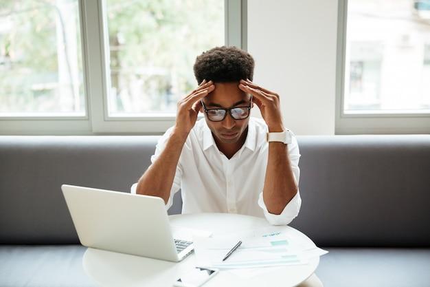 Konzentrierter ernsthafter junger afrikanischer mann, der coworking sitzt