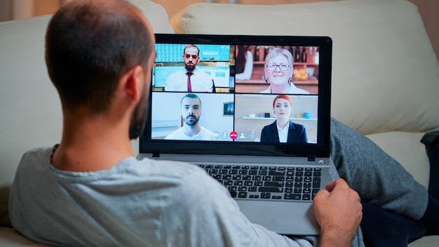 Konzentrierter erwachsener, der während einer videokonferenz einen laptop verwendet