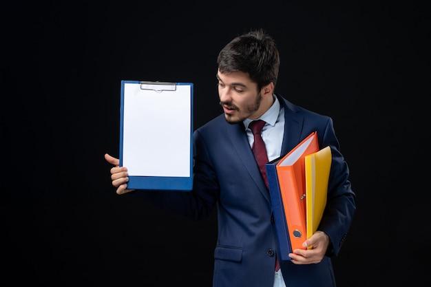 Konzentrierter erwachsener im anzug, der mehrere dokumente hält und eines davon an einer isolierten dunklen wand zeigt