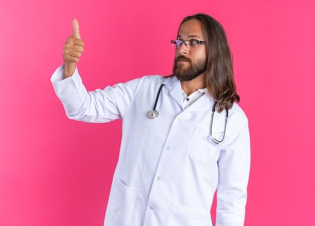 Konzentrierter erwachsener männlicher arzt, der ein medizinisches gewand und ein stethoskop mit einer brille trägt, die den daumen nach oben zeigt und seinen daumen isoliert auf rosa wand betrachtet