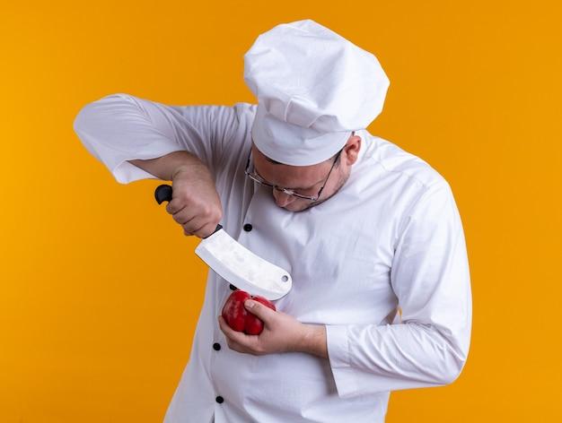Konzentrierter erwachsener männlicher koch mit kochuniform und brille, der pfeffer mit hackmesser berührt, der pfeffer einzeln auf orangem hintergrund betrachtet