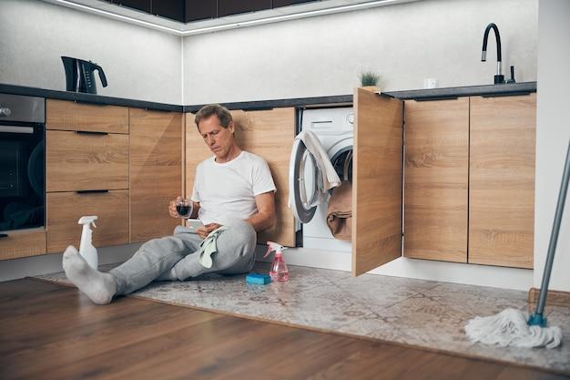Konzentrierter erwachsener mann, der auf sein smartphone starrt, während er eine nachricht liest, während er zu hause kaffee trinkt